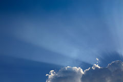 Sun rays through cloud above clear blue sky. Beautiful sun rays through cloud above clear blue heaven sky, sunlight in the summer day Stock Photo