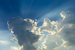 Sun rays through cloud above clear blue sky. Beautiful sun rays through cloud above clear blue heaven sky, sunlight in the summer day Royalty Free Stock Images