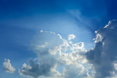 Sun rays through cloud above clear blue sky. Beautiful sun rays through cloud above clear blue heaven sky, sunlight in the summer day Royalty Free Stock Image