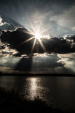 Sun rays behind clouds above the lake Royalty Free Stock Photos