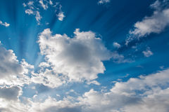 Sun rays and clouds. Bright sun rays through the white clouds with deep blue sky background, creating beautiful scenery Stock Photo
