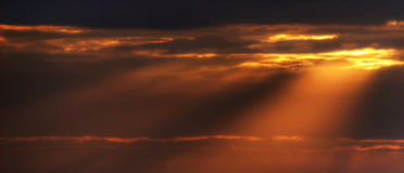 Sun rays through clouds. Sun rays piercing cloudy sky at sunset Stock Photo