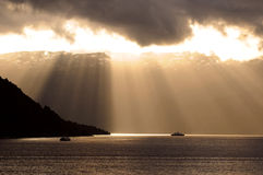 Sun rays through clouds. Golden sun rays through clouds falling on calm seawater Royalty Free Stock Images