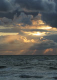 Sun rays through clouds. The golden rays of the sun breaking through the clouds over the  Baltic sea Stock Images