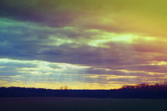 Sun rays through clouds above fields in Iowa before sunset Stock Photography