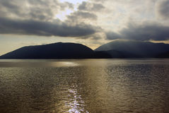 Sun rays through clouds above islands in Howe Stock Photo