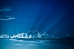 Sun rays through clouds in a blue sky Stock Photo