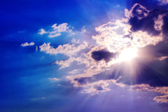 Sun rays and clouds Stock Images