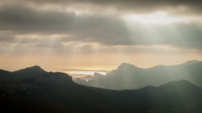 Sun rays through the clouds floating over the mountains and the sea. stock footage