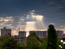 Sun rays through clouds illuminate new buildings Royalty Free Stock Image