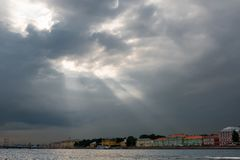 Sun rays through the clouds. RUSSIA, SAINT PETERSBURG - AUGUST 18, 2017: The sun`s rays breaking through the clouds on the University embankment of the Neva Stock Image
