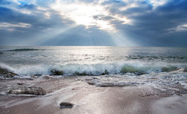 Sun rays through clouds. Sunbeams passing through clouds and warming sea Royalty Free Stock Photo