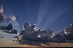 Sun rays through the clouds at a sunset time Stock Photography