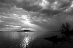 Sun rays coming out through the clouds over an island on a lake, with trees and trunks in the foreground stock photo