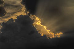 Sun rays through dark cloud Stock Images