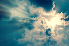 Sun rays with dark clouds. Background Stock Image