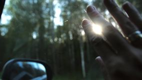 Sun rays through fingers and trees. Hand with rings on window of car on the go. Fingers palm. Close-up. Slow mo. Close-up of hand with rings on the window of car stock footage