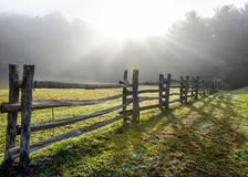 Sun Rays in Foggy Field and Split Rail Fence Royalty Free Stock Images
