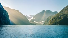 Sun rays on a foggy morning at Milford Sound. Looking towards Bowen Falls in Fiordland National Park. A small boat is part of numerous cruises available to Stock Photography