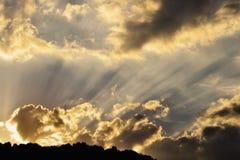 Sun rays on golden sky. Sun rays illuminating the dark clouds at sunset Stock Photography
