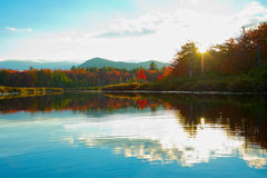 Sun rays illuminate peak foliage by mountain lake. Stock Images