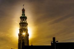 Sun rays through the Lange Jan Toren Long John Tower of the medieval Abbey from the Sun setting behind the tower in MIddelburg. Sun rays through the Lange Jan royalty free stock photos