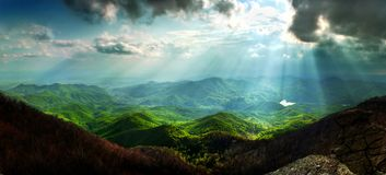 Sun rays mountain landscape. A beautiful landscape view with sun beams through clouds from the top of a mountain stock photo
