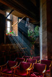 Sun rays over church window inside. A dim old church interior li Royalty Free Stock Image
