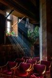 Sun rays over church window inside. A dim old church interior li Royalty Free Stock Image