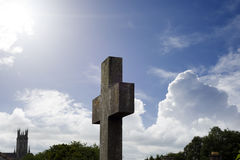 Sun rays over cross at ancient graveyard Stock Image