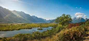 Sun rays over Glenorchy Lagoon in New Zealand. Glenorchy Lagoon view with the mountain range towards Mount Aspiring National Park in the background. Glenorchy is Stock Photos