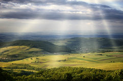 Sun rays over green hills. On a spring day Royalty Free Stock Images