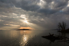 Sun rays over a lake. Sun rays coming out through the clouds over an island on a lake, with trees and trunks in the foreground Stock Photos