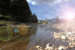 Sun rays over mountain river Stock Photo