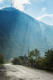 Sun rays over a mountain road Royalty Free Stock Image