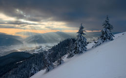 Sun rays over the mountain valley in winter Stock Images