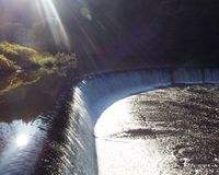 Sun rays over the water. The autumn sun shimmers above the dam in a river Stock Photos