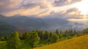Sun Rays Pass through the Clouds Over the Mountains at Sunset. stock footage