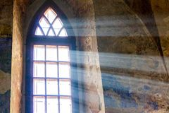 The sun rays penetrate by the window of the old church_. The sun rays penetrate by the window of the old church royalty free stock photo