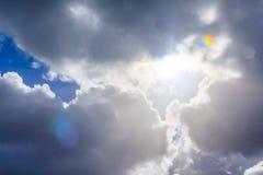 Sun Rays pierce the clouds and reach below. Sun rays pierce the clouds. Blue sky, dark blue clouds, Sun light coming through clouds. Lens flares Stock Photography