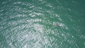 Sun rays play on ocean water with surfer figure stock video