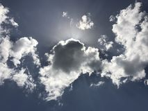 Sun Rays Shine behind White Clouds Stock Photo