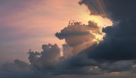 Sun rays shining through beautiful rain clouds at dusk. Dramatic cloudscape at sunset Stock Images