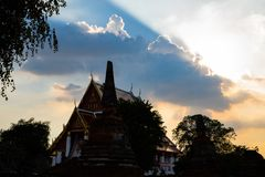 Sun rays shining from behind a big cloud aboce thai temple stock photos
