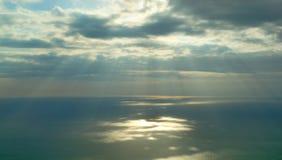 Sun rays shining through clouds. Over sea Stock Image