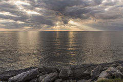 Sun rays shining through clouds over the ocean Royalty Free Stock Photos