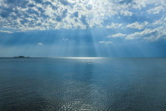 Sun rays shining through the clouds over the sea Stock Photography