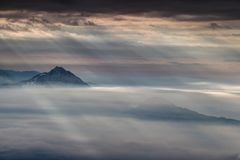 Sun rays shining through dark clouds illuminate conical peaks. Curtain of sun rays shining through dark gray clouds illuminates two conical mountains in autumn Royalty Free Stock Photo