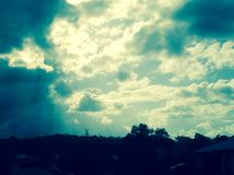 Sun rays shining through Dark Clouds Royalty Free Stock Photos