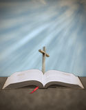 Sun rays shining down on cross with bible Royalty Free Stock Photos